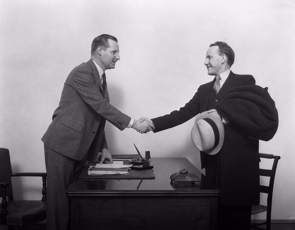 Stock Photo: 4186-13569 1930S Two Men Shaking Hands At Desk In Office