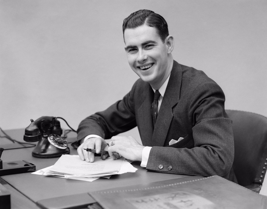 Stock Photo: 4186-13590 1930S Man Sitting At Desk In Office Holding Pen Smiling
