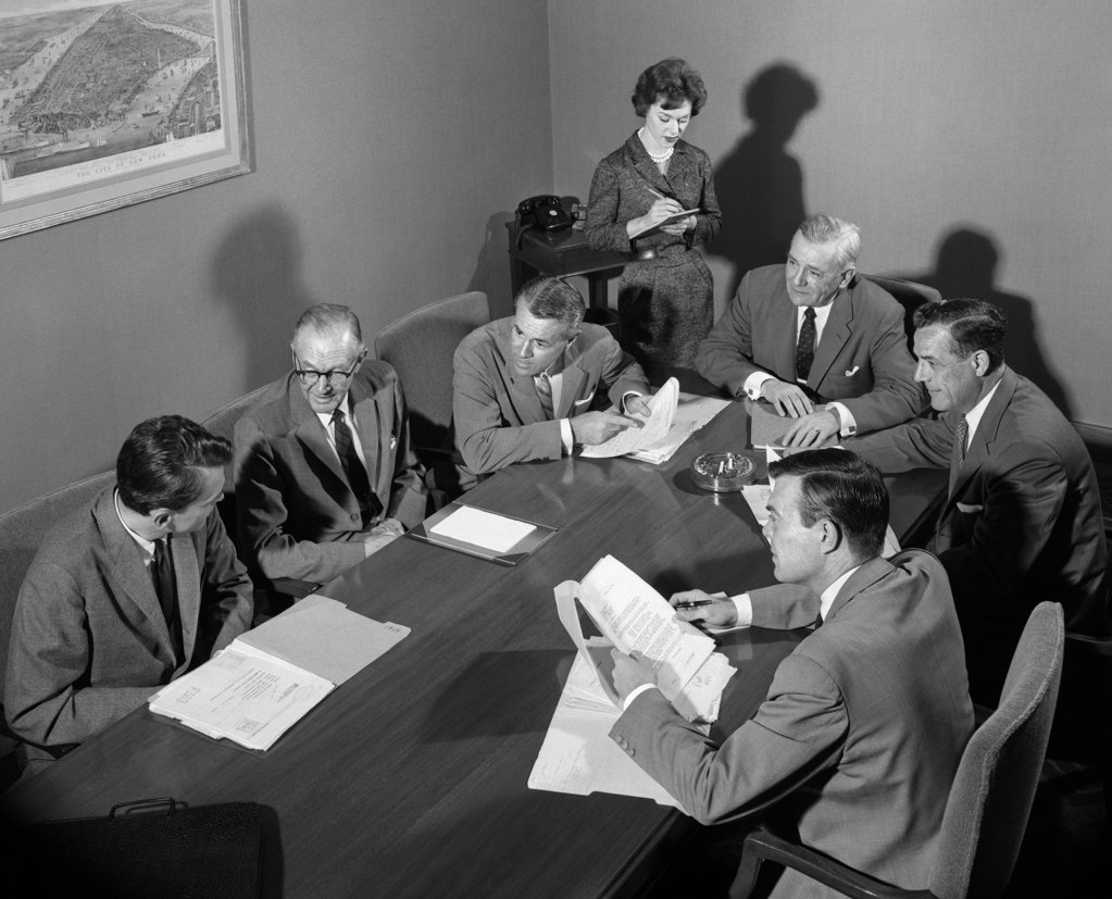 Stock Photo: 4186-13592 1950S Group Of Businessmen Having Meeting Around Table Female Secretary Takes Notes Indoor