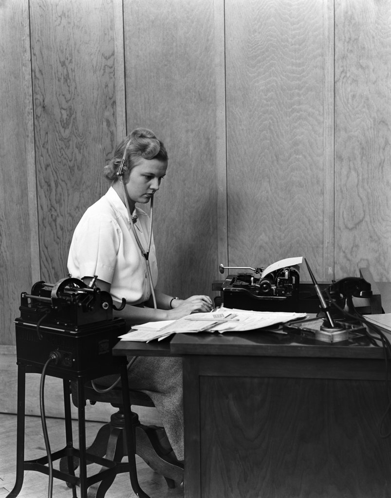 Stock Photo: 4186-13600 1930S Woman Secretary At Business Office Deck Transcribing From Dictaphone Dictation Voice Recording Machine