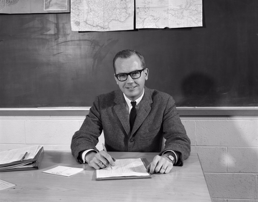 Stock Photo: 4186-13665 1960S Man Teacher At Desk In Classroom Pencil Paper In Front Blackboard Background Smiling At Camera