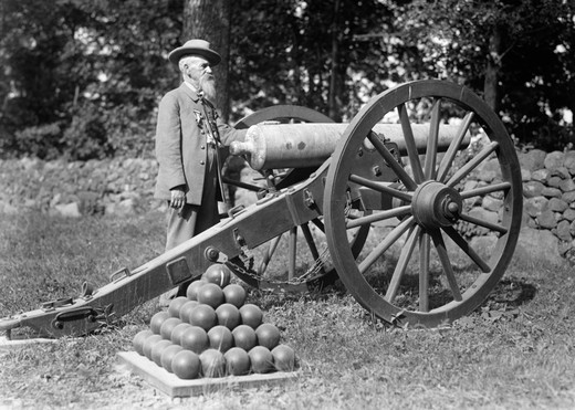 Stock Photo: 4186-13767 1890S 1900S Elderly Bearded Man Confederate Civil War Veteran With Military Decorations On Coat Standing Next To Cannon