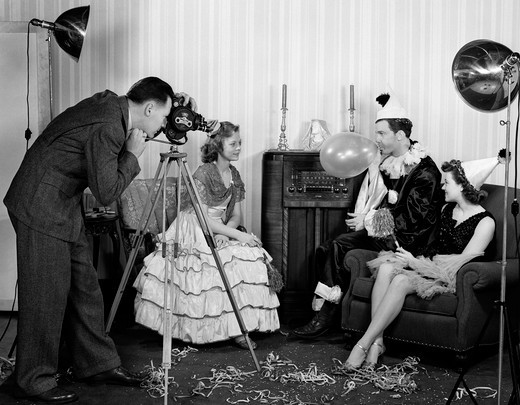 Stock Photo: 4186-13787 1940S Photographer Taking Picture Of Two Women & A Man Wearing Costumes Man Blowing Up Balloon