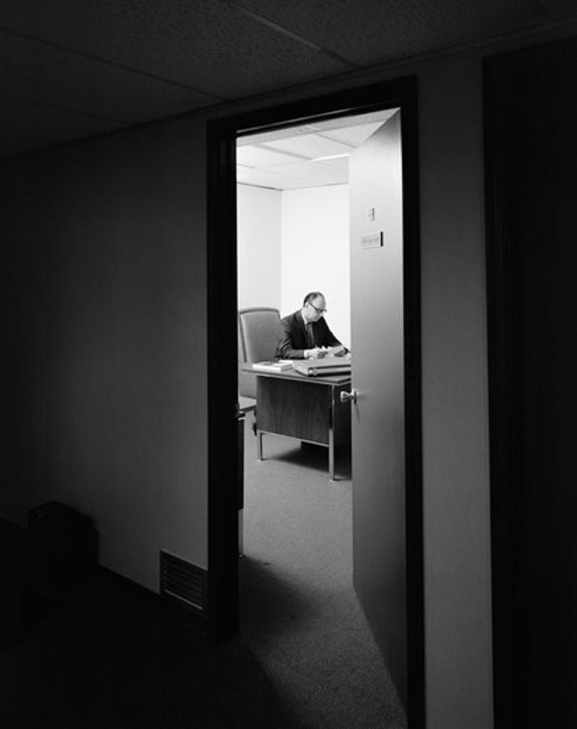 Stock Photo: 4186-13797 1960S 1970S Executive Businessman At Desk Seen Working Late Through Door Ajar