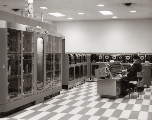 Stock Photo: 4186-13816 1950S Man Programmer Sitting At Console In Data Processing Room With Remington Rand Univac Computer And Tape Drives