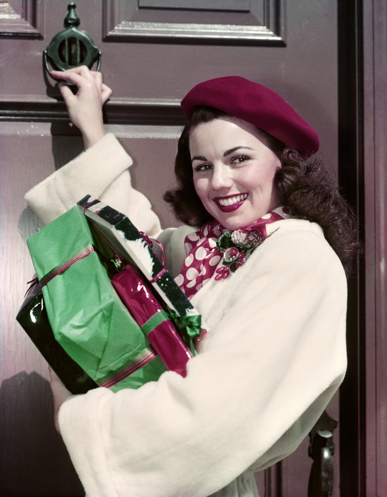 Stock Photo: 4186-14043 1950S Smiling Woman Carrying Christmas Presents Knocking On House Door