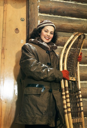 Stock Photo: 4186-14158 1940S 1950S Brunette Woman By Log Cabin Holding Snowshoes