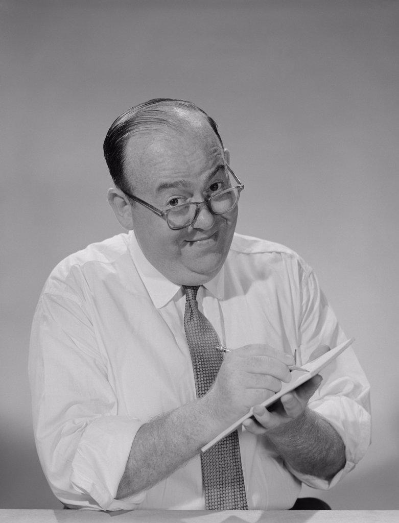 1950S 1960S Balding Businessman Wearing Eyeglasses Shirt Sleeves Smiling Writing Notepad : Stock Photo