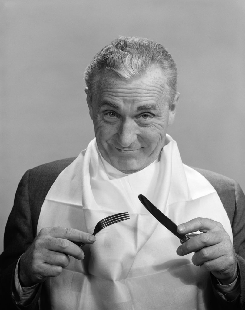1950S 1960S Elderly Man Wear Napkin As Bib Smiling Holding Knife & Fork Eat Dine Anticipation Food Diet Nutrition : Stock Photo