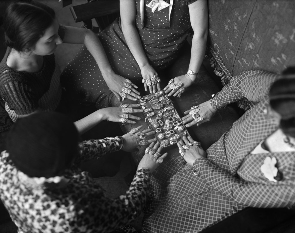 Stock Photo: 4186-14376 1920S Four Women With Rings On All Fingers Looking At A Tray Of Jewelry