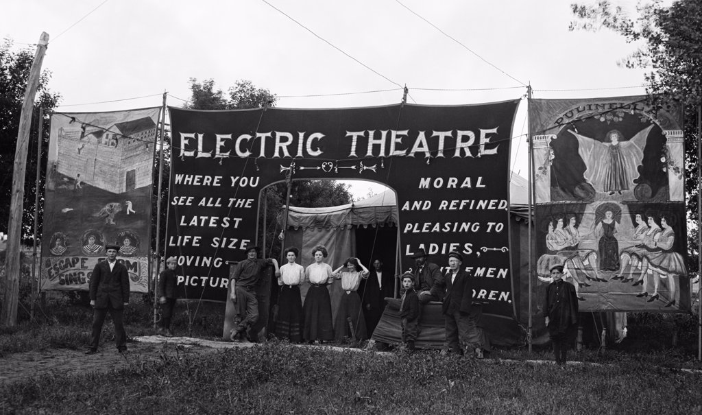 Stock Photo: 4186-14446 1900S 1910S Group People Standing At Entrance Outdoor Traveling Moving Picture Theater