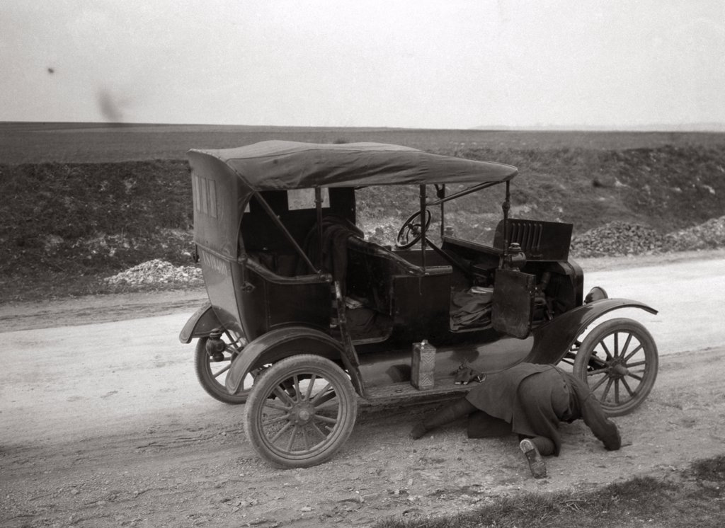 Stock Photo: 4186-14531 1920S 1930S Man On His Hands And Knees Looking Under Model T Broken Down On Roadside
