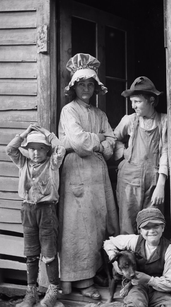 1900S 1910S Poor Rural Family Mother And Three Sons At Cabin Door Ozark Hills Missouri Usa : Stock Photo