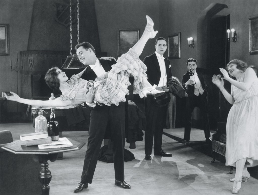 1920S Movie Still Of Wild Party With Woman Flapper Turned Upside-Down In Arms Of Man Dancing : Stock Photo