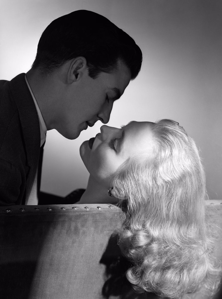 1940S 1950S Movie Star Studio Style Romantic Couple Embracing On Sofa About To Kiss Husband Silhouette Wife Long Blond Hair : Stock Photo
