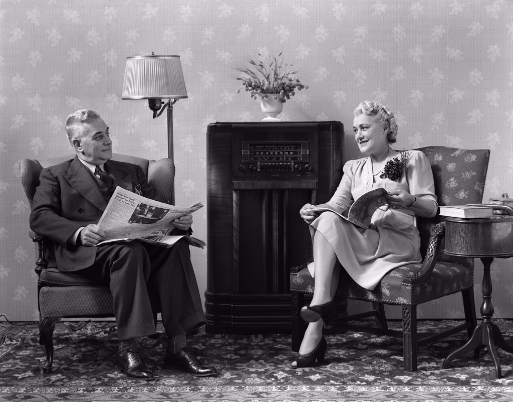 1940S Senior Couple Sitting In Living Room Reading Newspaper And Magazine Listening To Radio : Stock Photo