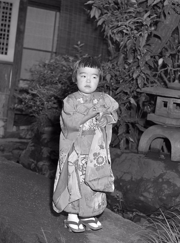 Stock Photo: 4186-15113 1960S Mari Small Geisha Little Girl In Native Japanese Costume Kimono Robe Obi Tongs Asian Culture