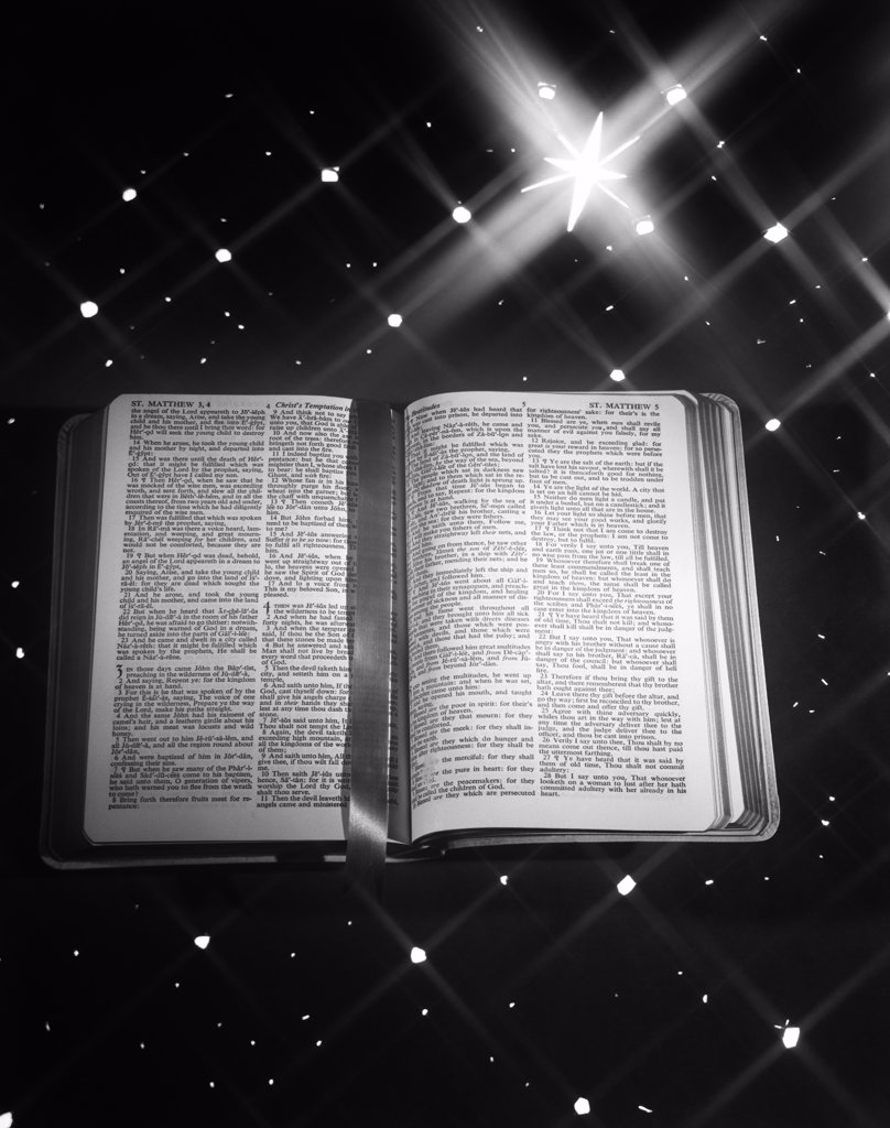 Stock Photo: 4186-15158 1950S Open Book Bible Ribbon Bookmark Matthew Against Star Background Large Star Of Bethlehem Christmas