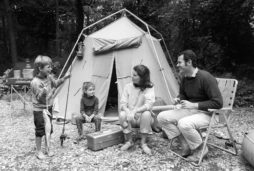 Stock Photo: 4186-1518 1970S Family Of Four Sitting In Front Of Tent In Woods Son Holding Fishing Pole In One Hand & Big Fish In Other