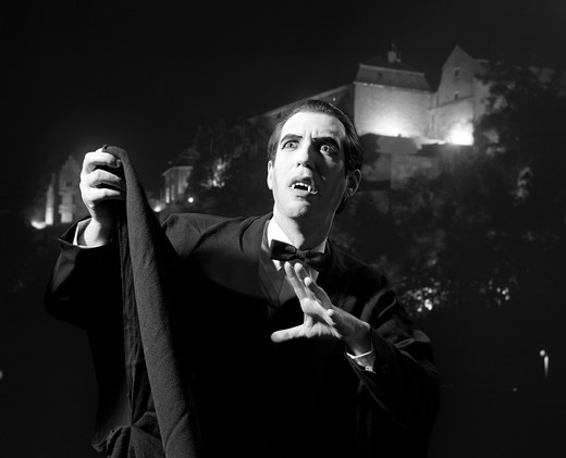 Nighttime Portrait Of Man Wearing Cape And Fangs Dressed As Dracula : Stock Photo