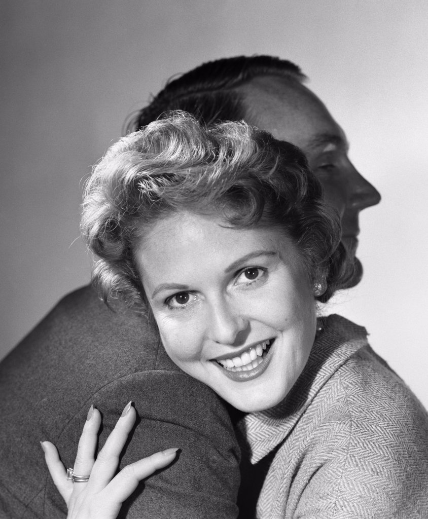 1950S Smiling Woman Hugging Man Head On His Shoulder : Stock Photo