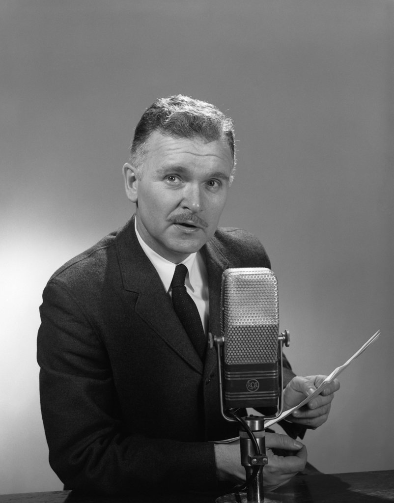 Stock Photo: 4186-15334 1950S 1960S Older Man Speaking Into Microphone Holding Papers Radio Television Newsman Reporter Announcer