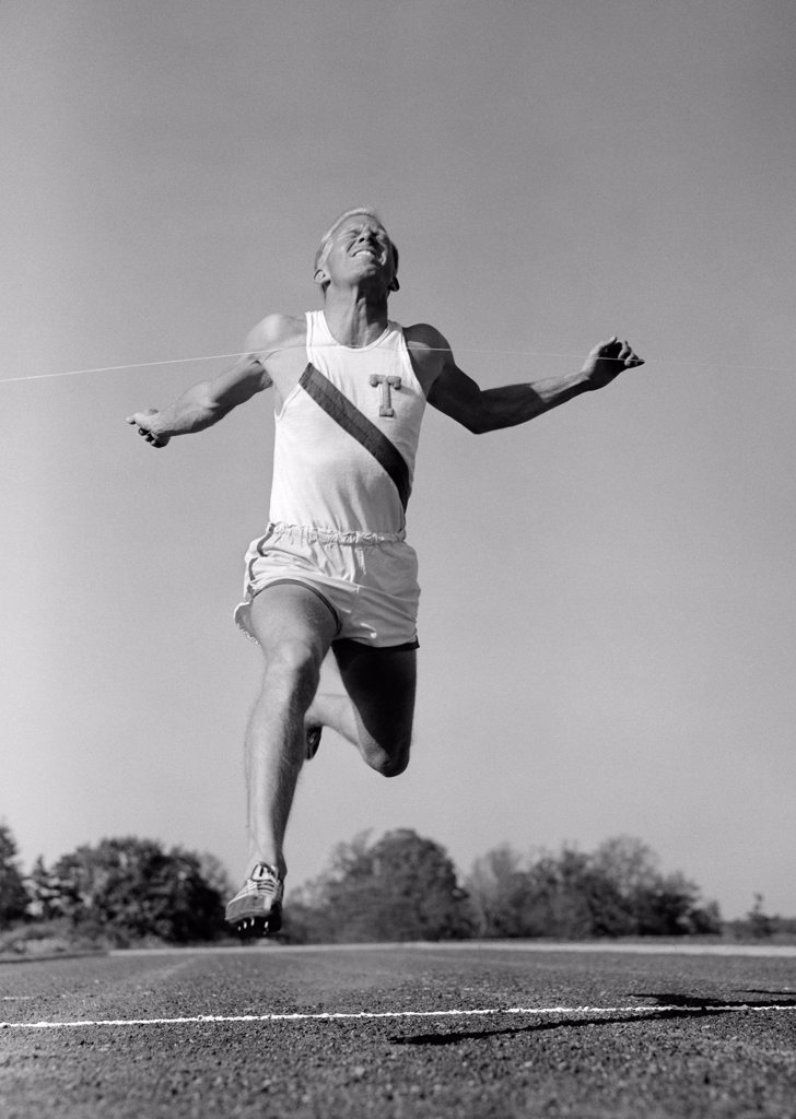 1960S Man Running Winning Sprinting Across The Finish Line Outdoor : Stock Photo