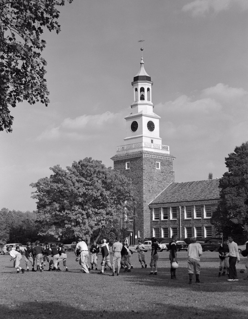 Stock Photo: 4186-15809 1950S School Football Team Practicing On Lawn In Front Of Stone Campus Building With Clock Tower