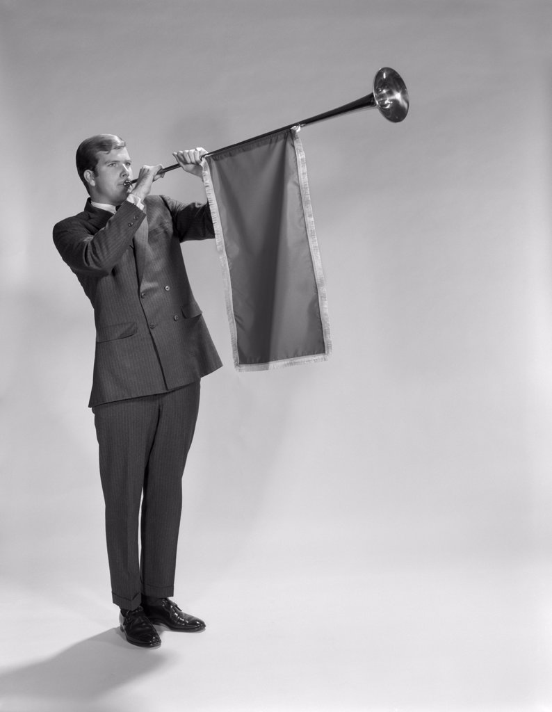 1960S Young Man Standing Blowing Herald'S Horn : Stock Photo