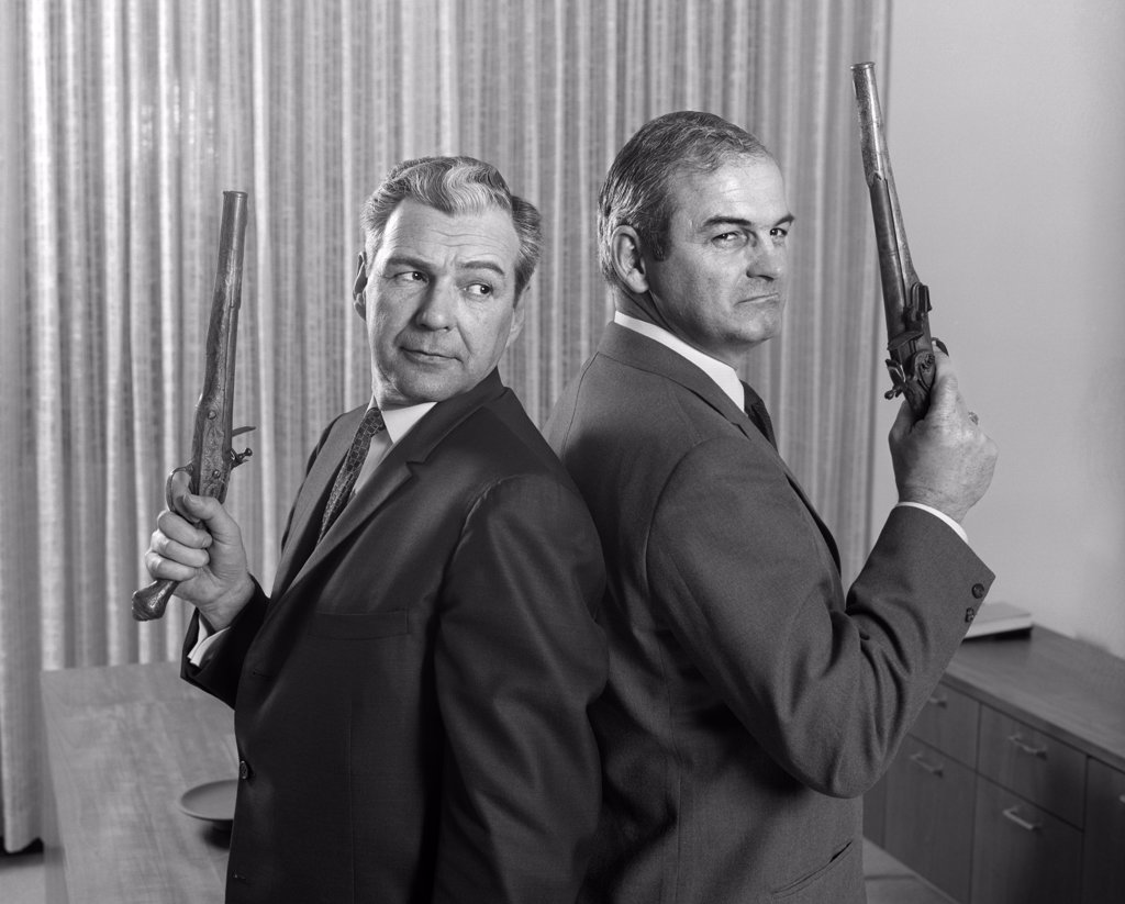 Stock Photo: 4186-15904 1960S 2 Middle Aged Men Back To Back Holding Duel Pistols Guns