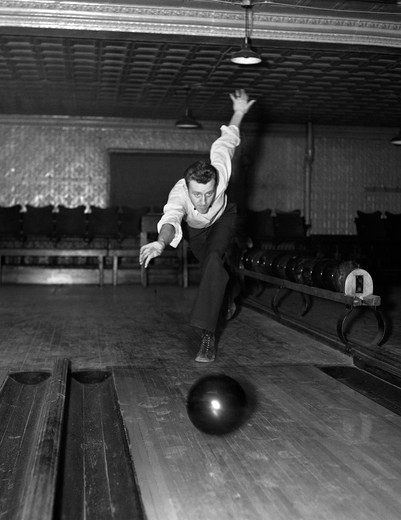 Stock Photo: 4186-16023 1930S Man Bowling Just Releasing Ball Into Alley