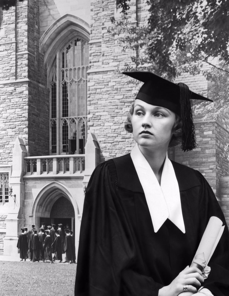 Stock Photo: 4186-16156 1930S Woman Graduate Cap Gown Holding A Diploma Standing In Front Stone Building Sad Serious Expression