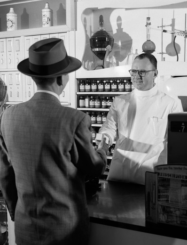 Stock Photo: 4186-16354 1950S Pharmacist Giving Prescription To Man Customer