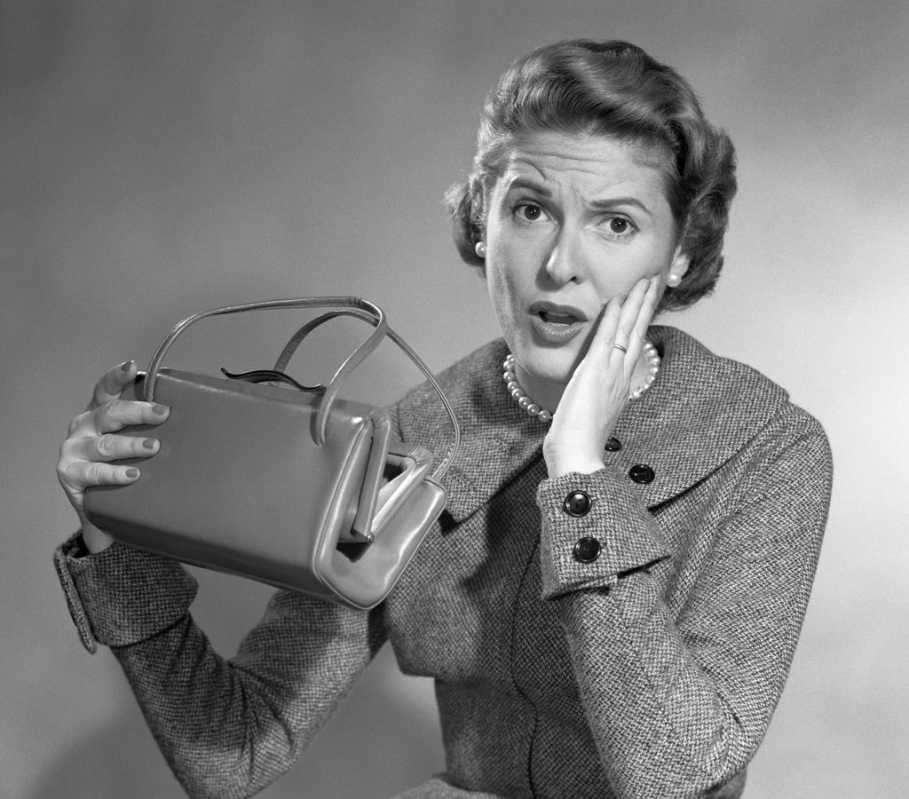 Stock Photo: 4186-16462 1950S Woman Funny Surprised Oh No Facial Expression Hand Cheek Look Empty Hand Bag Pocketbook Broke