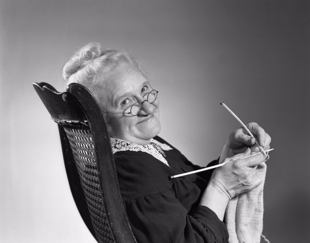 Stock Photo: 4186-16473 1950S 1960S Senior Elderly Woman Knitting Smiling Turning To Look At Camera Granny Glasses