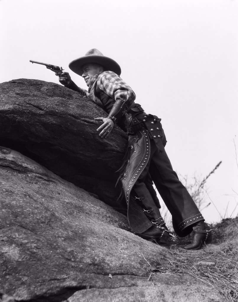 Stock Photo: 4186-1666 1920S Cowboy Among Rocks Aiming Revolver