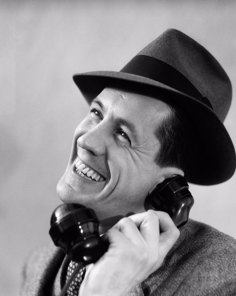 Stock Photo: 4186-16664 1930S Close-Up Of Man In Suit And Fedora Hat Smiling While Talking On Phone