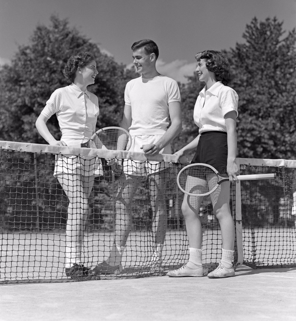Stock Photo: 4186-16666 1940S 1950S Two Girls And A Guy Tennis Players Holding Rackets And Tennis Ball Standing Near Net On Court