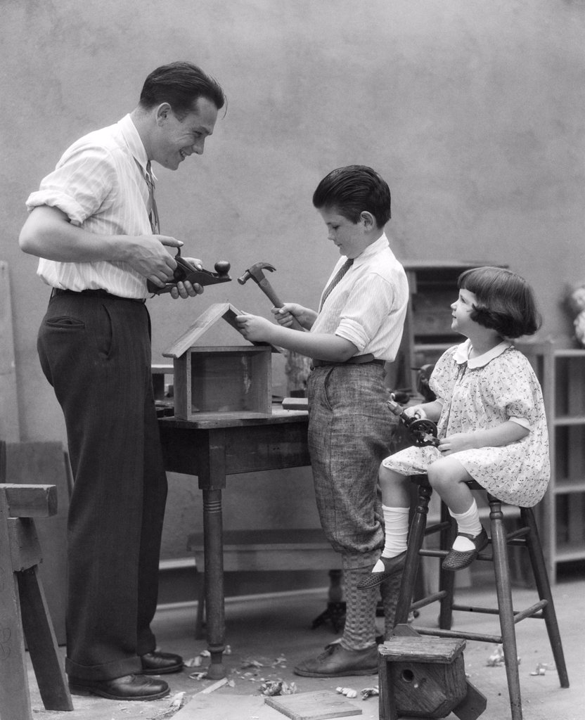 Stock Photo: 4186-16836 1920S Family Father Carpenter Teaching Son And Daughter To Build A Birdhouse With Woodworking Tools