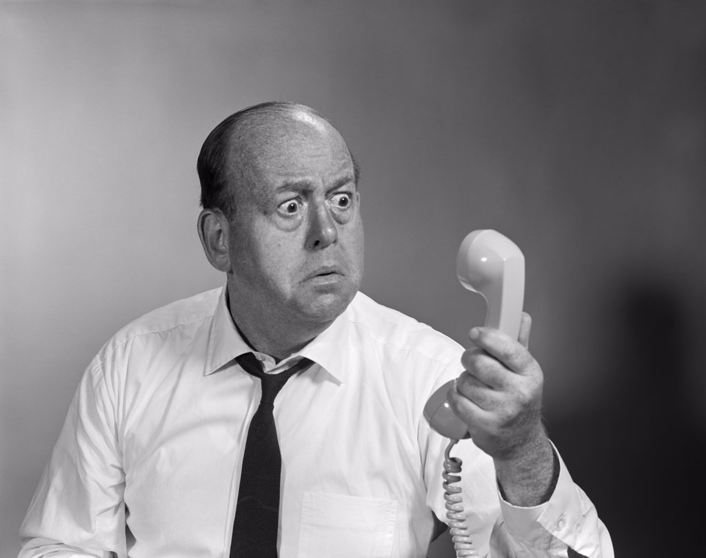 Stock Photo: 4186-16848 1960S Balding Man Looking Angry Into Telephone Receiver