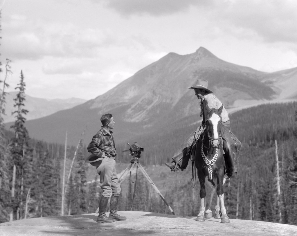 1930S Cameraman In Boots Jodhpurs & Wool Hunting Shirt Standing Next To Movie Camera On Tripod Talking To Mounted Cowboy : Stock Photo