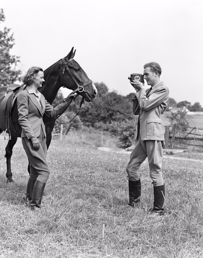 Stock Photo: 4186-16892 1940S Smiling Equestrian Couple The Woman Is Holding The Horse Bridle While The Man Is Taking Home Movie