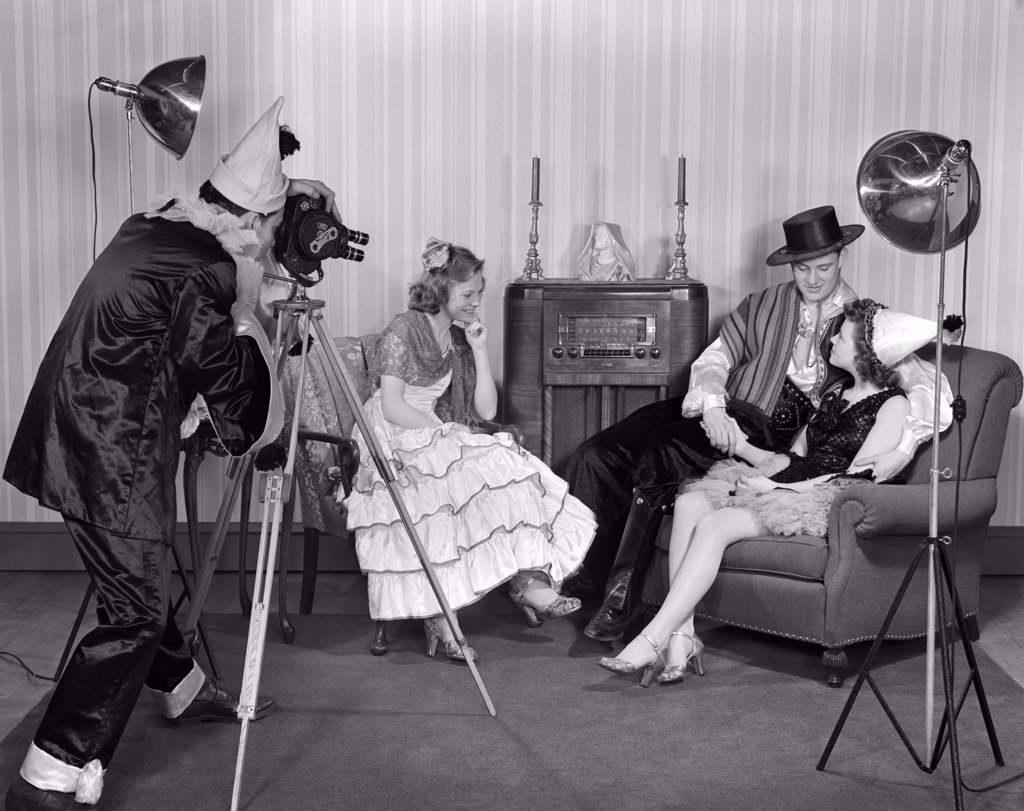 Stock Photo: 4186-16893 1940S Costumed Group Of Teenage Men & Women Filming With A Movie Camera In A Living Room With Armchairs And Floor Model Radio