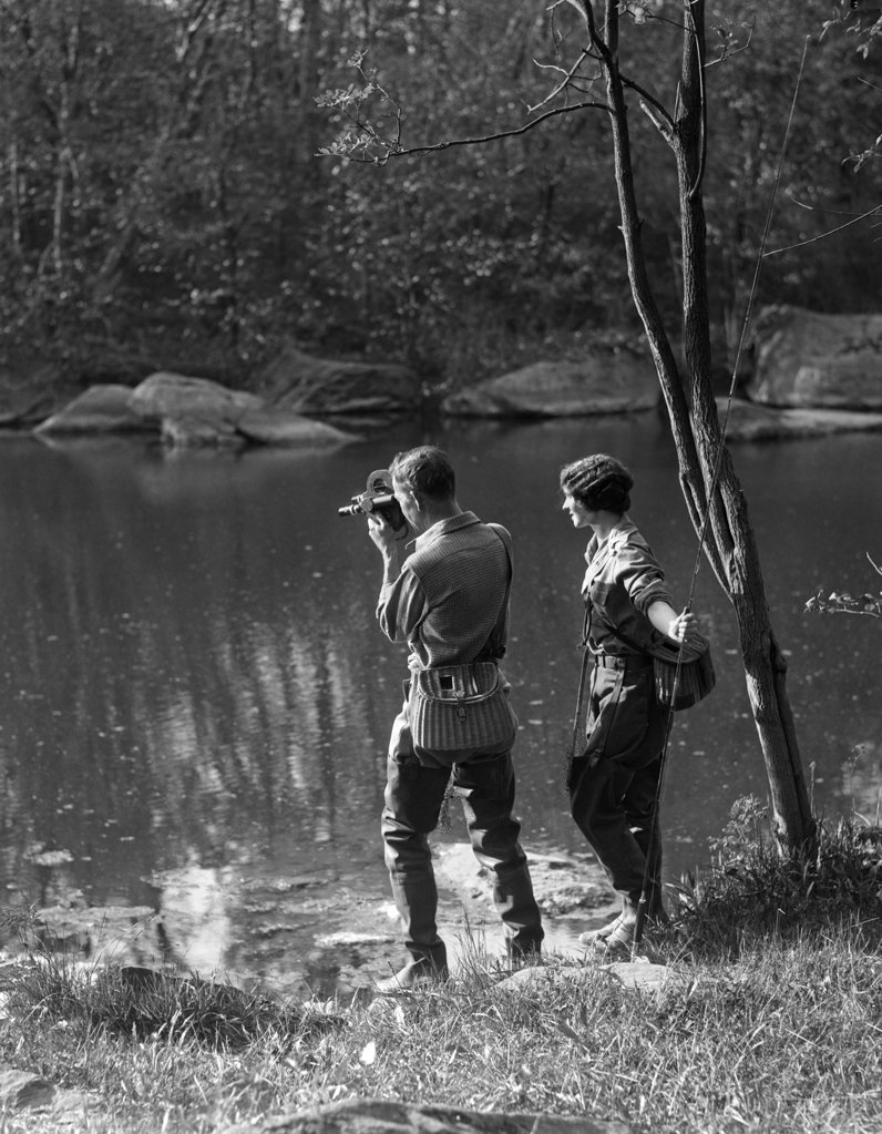 1930S Man With Movie Camera & Woman With Trout Fishing Rod Both Are Wearing Waders & Wicker Creels : Stock Photo
