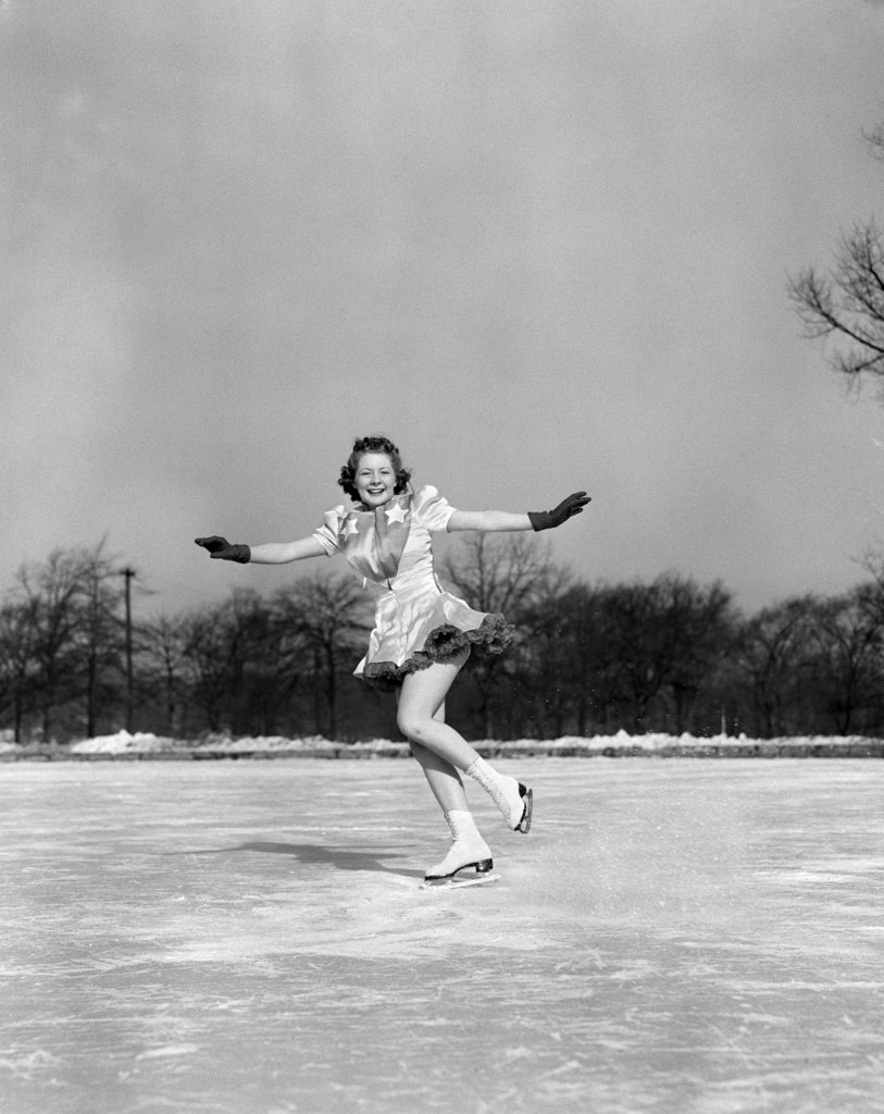 1940S Smiling Woman On Ice Outdoors Ice Skating Arms Out About To Do Backward Jump : Stock Photo
