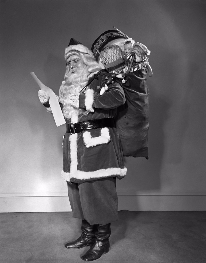 Stock Photo: 4186-17047 1940S Santa Claus Carrying Bag Full Of Toys Reading List