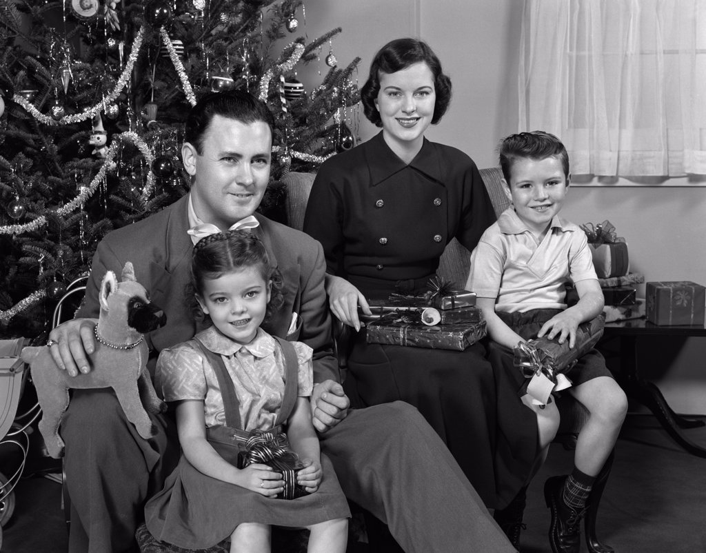 Stock Photo: 4186-17110 1940S 1950S Family Sitting Around Christmas Tree Holding Gifts Looking At Camera