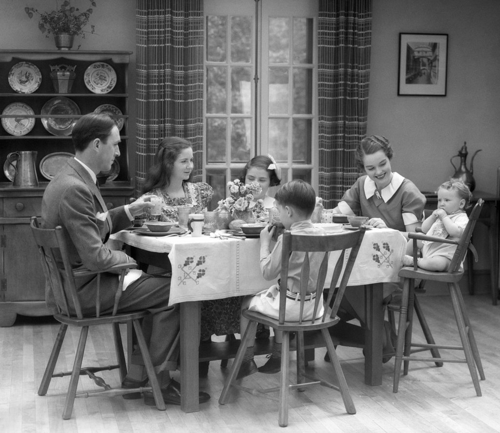 Stock Photo: 4186-1956 1930S Family Of 6 Sitting At The Table In A Dining Room Eating Breakfast The Baby Is Sitting In A High Chair