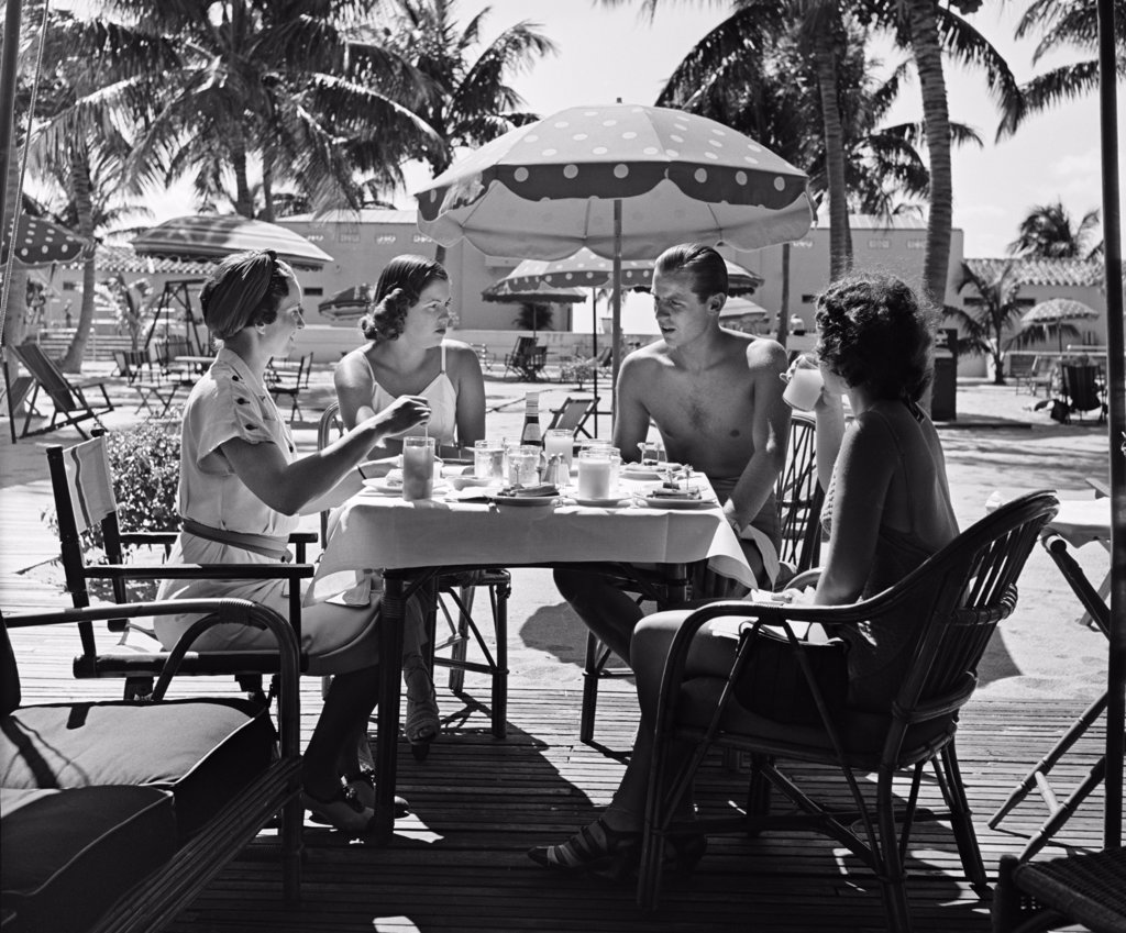 Stock Photo: 4186-1998 1950S Three Women And One Man Sitting At Tropical Pool Side Table Talking