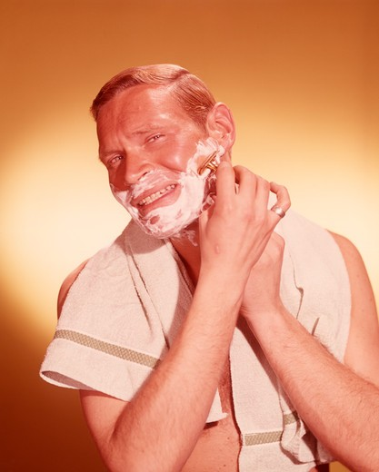 Stock Photo: 4186-2188 1960S Man Looking As If In Bathroom Mirror Shaving Face With Razor Towel Around Neck
